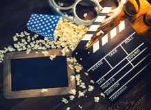 Cinema concept of vintage film reel with popcorn. Cinema concept of vintage film reel with popcorn on old wooden background Royalty Free Stock Images