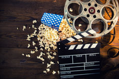 Cinema concept of vintage film reel with popcorn. Cinema concept of vintage film reel with popcorn on old wooden background Stock Photography