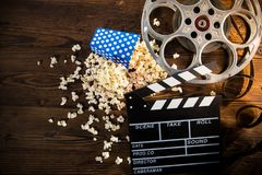 Cinema concept of vintage film reel with popcorn. Cinema concept of vintage film reel with popcorn on old wooden background Stock Photos