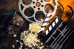 Cinema concept of vintage film reel with popcorn. Cinema concept of vintage film reel with popcorn on old wooden background Royalty Free Stock Photos