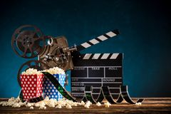 Cinema concept of vintage film reel with popcorn. Cinema concept of vintage film reel with popcorn on old wooden background stock images