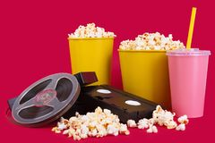 Cinema concept of vintage film. Reel with popcorn on a red background Royalty Free Stock Photo