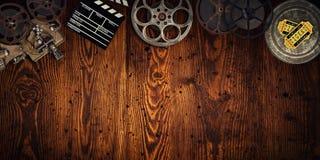 Cinema concept of vintage film reels, clapperboard and projector. Cinema concept of vintage film reels, clapperboard and projector on old wooden background stock photography
