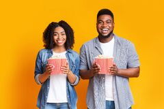 Cinema Date. Happy African American Couple With Popcorn Buckets Over Yellow Background