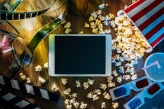 Cinema and entertainment app. Digital touch screen tablet with popcorn, 3D glasses and filmstrip; movie online streaming cinema and entertainment concept Stock Photo