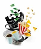 Cinema or film entertainment concept. With floating clapperboard, film canister coffee, orange juice, popcorn, nachos and dip over white with copy space stock photography