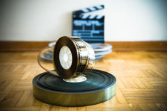 Cinema film reel and out of focus movie clapper board Stock Images