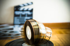 Cinema film reel and out of focus movie clapper board Stock Image