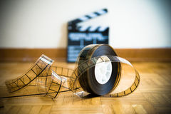 Cinema film reel and out of focus movie clapper board. 35 mm cinema film reel and out of focus movie clapper board in background on wooden floor Stock Photos