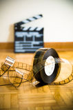 Cinema film reel and out of focus movie clapper board Royalty Free Stock Photography