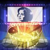 The Cinema. Film strip and wide movie screen against rays of cinema projector against festive background Royalty Free Stock Image