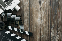 Cinema and filmmaking. Vintage film camera, filmstrip and clapper board on a wooden desktop, cinema and filmmaking concept Stock Image