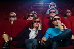 In a cinema. Group of people in 3D glasses watching movie in cinema royalty free stock photos
