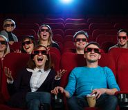 In a cinema. Group of people in 3D glasses watching movie in cinema Stock Image