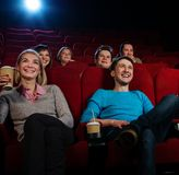 In a cinema. Group of smiling people watching movie in cinema stock images