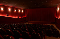In a cinema hall. Red cinema hall in theatre with armchairs and lights royalty free stock photography