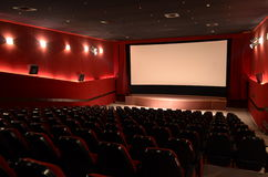 In a cinema hall. Red cinema hall in theatre with armchairs and lights royalty free stock photos