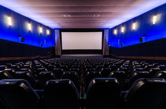 In cinema theater. Dark blue auditorium in cinema theater. The white screen in foreground Stock Images