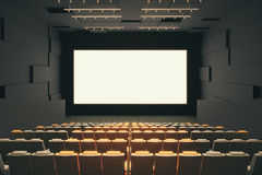 Cinema hall interior. With rows of seats, patterned walls, ceiling with lamps and blank white screen. Mock up, 3D Rendering Royalty Free Stock Image