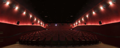 In a cinema hall. Red cinema hall in theatre with armchairs and lights royalty free stock image