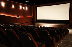 In the cinema hall. Red cinema hall in theatre with armchairs and lights royalty free stock photo