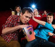 In a cinema. Impudent young men steal popcorn in cinema while people watching movie stock photography