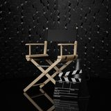 Cinema Industry Concept. Director Chair, Movie Clapper and Megap. Hone on a black background. 3d Rendering Royalty Free Stock Photo