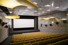 Cinema interior. Empty cinema auditorium with line of yellow chairs, stage and projection screen. Ready for adding your own picture Royalty Free Stock Images