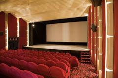 Cinema interior. Empty cinema auditorium with line of chairs and projection screen. Ready for adding your own picture. Side view Stock Photography