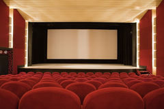 Cinema interior. Empty cinema auditorium with line of chairs and projection screen. Ready for adding your own picture. Front view Stock Photo
