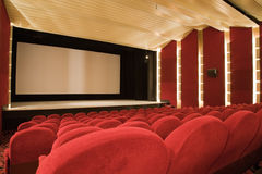 Cinema interior. Empty cinema auditorium with line of chairs and projection screen. Ready for adding your own picture. Side view Royalty Free Stock Photography
