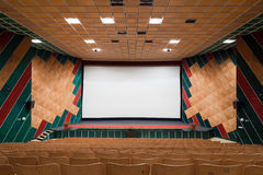 Cinema interior. Empty cinema auditorium with line of chairs and projection screen. Ready for adding your own picture. Front view Royalty Free Stock Photo