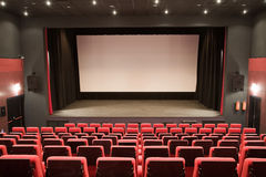 Cinema interior. Empty cinema auditorium with line of chairs and stage with silver screen. Ready for adding your own picture Stock Photo