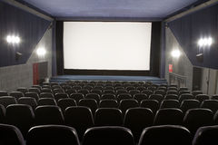 Cinema interior. Empty cinema auditorium with line of chairs and stage with silver screen. Ready for adding your own picture Stock Photography