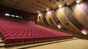 Cinema interior. Interior of cinema auditorium with walls and ceiling decoration and line of pink chairs Stock Photography