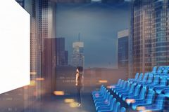 Cinema interior, blue chairs, screen, side toned. Young African American woman looking at the screen in a modern cinema interior with gray and dark wooden walls Stock Image