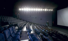 Cinema interior with lights on. Chairs and screen. Stock Image