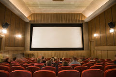 Cinema interior with people. Old retro style cinema auditorium with line of red chairs, sitting visitors and silver screen. Ready for adding your own picture Royalty Free Stock Images