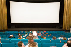 Cinema interior with people. Cinema auditorium with people waiting in green chairs on movie performance. Ready for adding your own picture Stock Photo