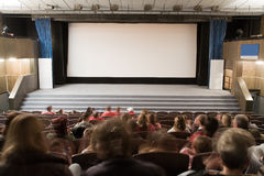Cinema interior with people. People in cinema auditorium with line of violet chairs and silver screen are waiting for movie performance. Ready for adding your Royalty Free Stock Images