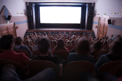 Cinema interior with people. Cinema auditorium with people in chairs watching movie performance. Ready for adding your own picture Stock Images