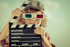 Cinema. Kid holding clapper board against summer sky background. Cinema concept Stock Image