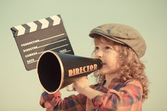 Cinema. Kid holding clapper board against summer sky background. Cinema concept Royalty Free Stock Images