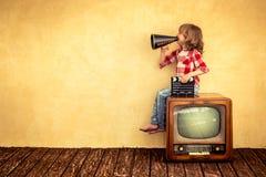 Cinema. Kid shouting through vintage megaphone. Communication concept. Retro TV Stock Images