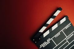 Cinema minimal concept. Watching film in the cinema. clapper board on red background. stock photography