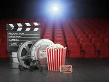Cinema, movie or home video concept background. Film reels, clap. Per board  and pop corn in the theater movie cinema screen with empty seats. 3d illustration Royalty Free Stock Image