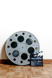 Cinema movie roll with clapper on wooden floor Royalty Free Stock Images