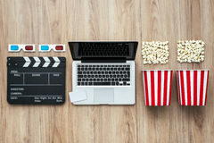 Cinema movie streaming. Laptop, clapper board, popcorn and 3D glasses: cinema streaming and movie series online concept Royalty Free Stock Photos