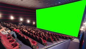 Cinema movie theater auditorium with viewers, red chairs and green projection screen timelapse