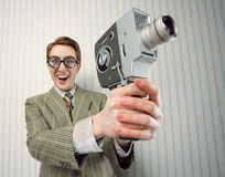 Cinema. Nerdy young man using old fashioned cine camera Royalty Free Stock Image
